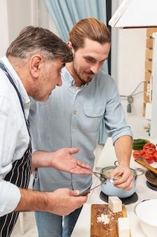 Hijo y padre confundido cocinando