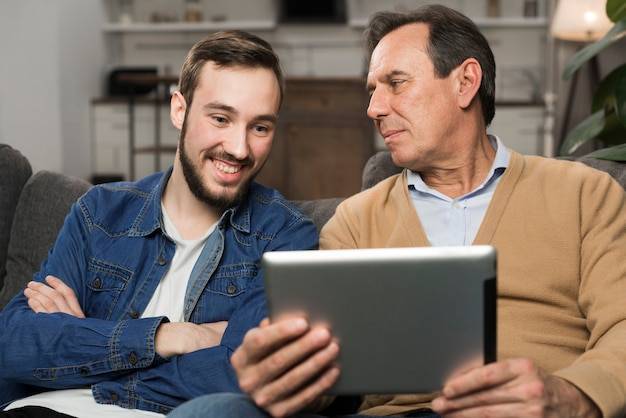 Hijo y padre sonriendo a la tableta en la sala de estar