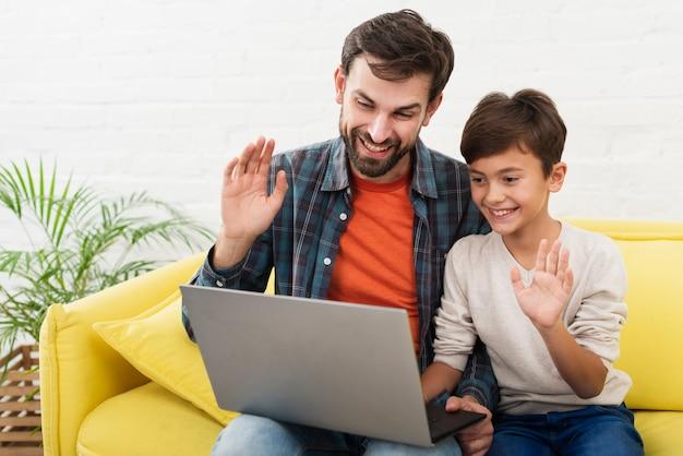 Hijo y padre sosteniendo una laptop y saludando