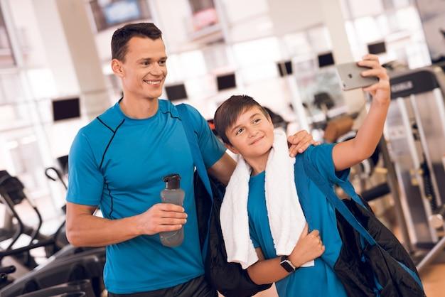 Hijo y papá tomando selfie en el gimnasio.