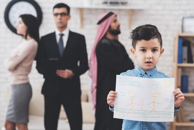 El hijo está de pie con un dibujo feliz, los padres están discutiendo.