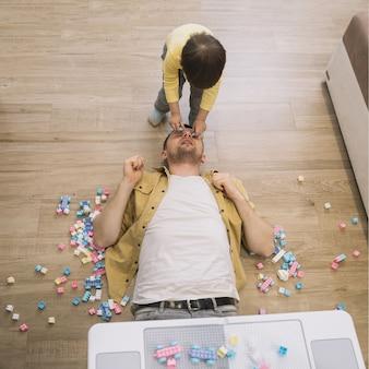 Hijo poniendo piezas de lego de la cara del padre