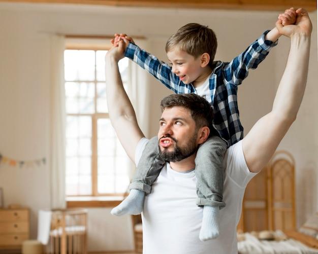 Hijo sentado sobre los hombros de su padre.