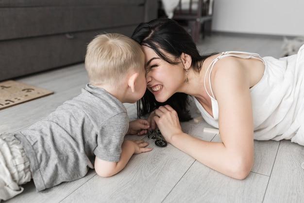 Hijo y su madre acostados en el piso de madera frotándose la nariz