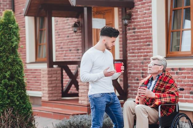 Hijo con su padre sosteniendo café y hablando con papá. hora del café