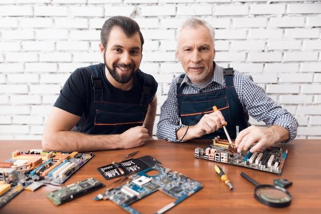 El hijo y el viejo padre hacen la reparación del dispositivo en el taller.