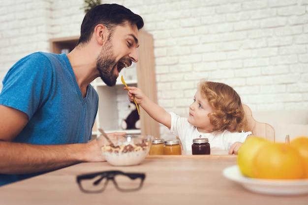 Hijos está alimentando a su padre un desayuno en casa.
