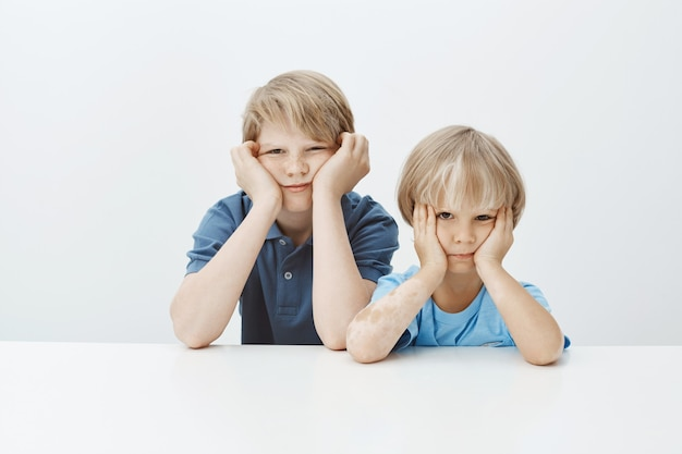 Hijos castigados por mal comportamiento en la escuela. niños varones lindos infelices aburridos sentados en la mesa