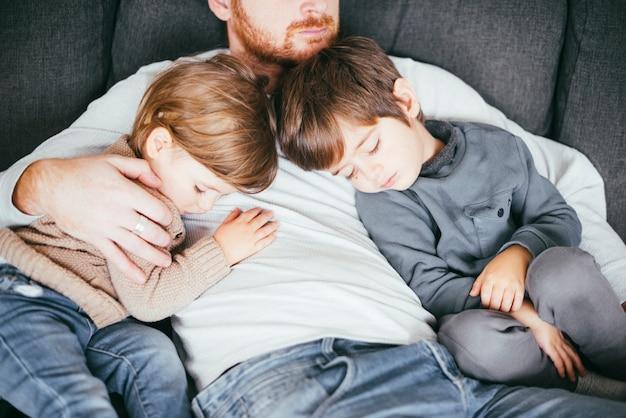 Hijos siestas en el pecho del padre