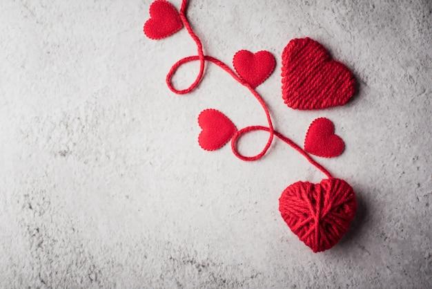 Hilado rojo en forma de corazón en el fondo de la pared
