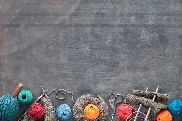 Hilados de lana y agujas de tejer, fondo de tejer creativo oscuro con espacio de copia
