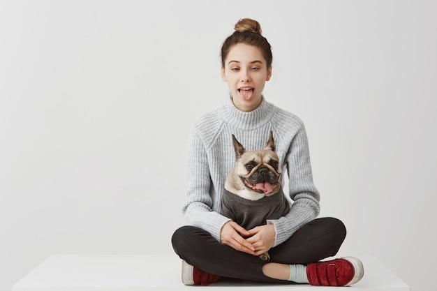 Hilarante mujer de 20 años posando con la lengua fuera. tiro divertido de la muchacha adulta joven que engaña copiando a su perro mientras se sientan juntos en la mesa concepto de alegría, espacio de copia