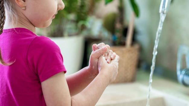 Hild se lava las manos con jabón en casa. concepto de protección contra virus.