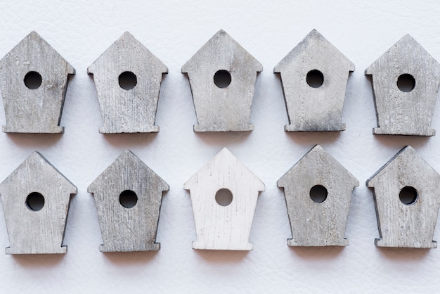 Hilera de casas de madera de aves sobre fondo blanco con textura