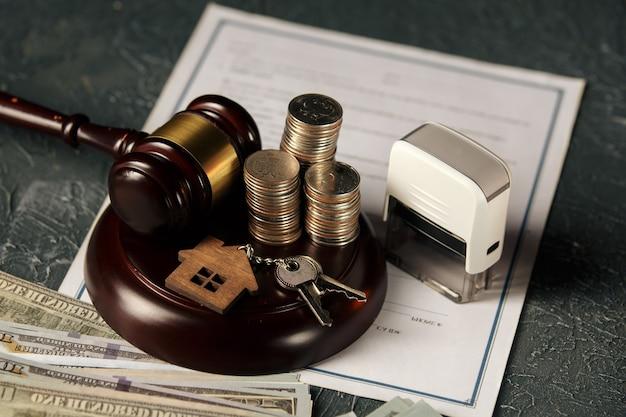 Una hilera de monedas en un modelo de casa pequeña y un martillo de subasta de ley.