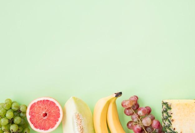 Hilera de uvas; pomelo; melón; plátano; uvas y piña sobre fondo pastel