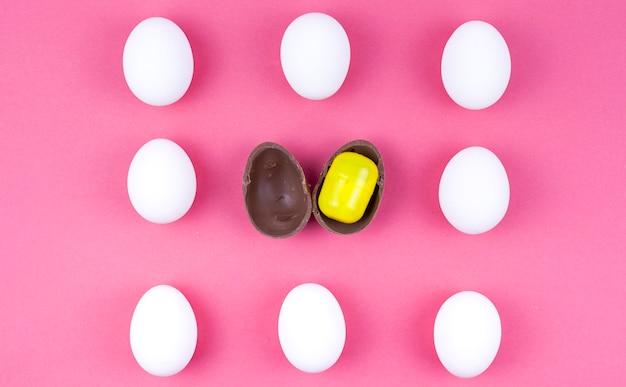 Hileras de huevos de gallina blanca con huevo de chocolate con sorpresa.