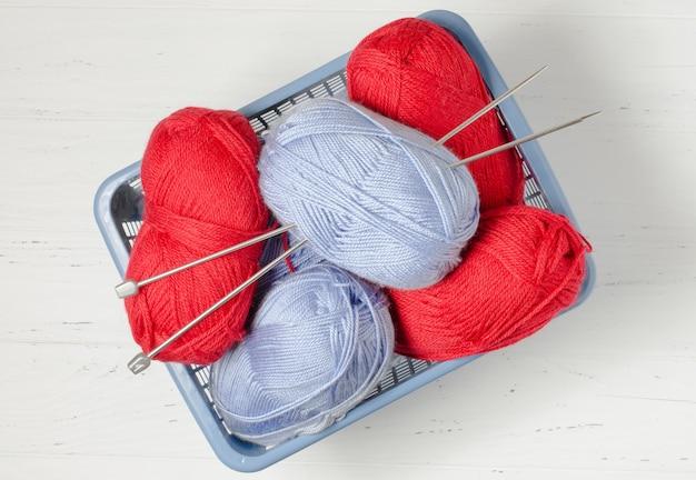 Hilo azul y rojo en una canasta de plástico