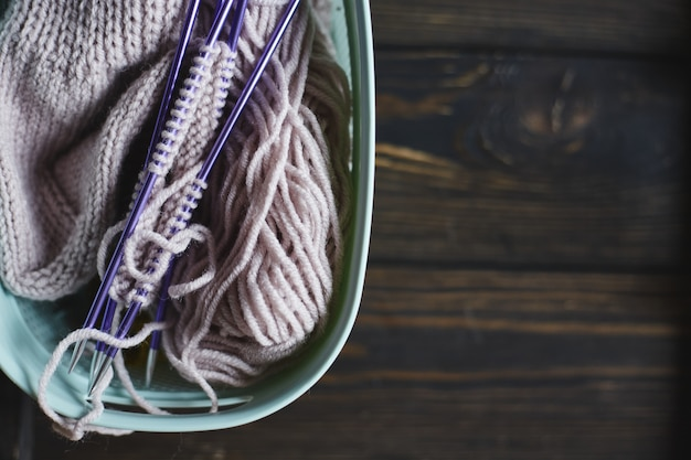 Hilo en bobinas y agujas de tejer sobre mesa de madera. pasatiempos caseros. calcetín tejido a mano con agujas y ovillo