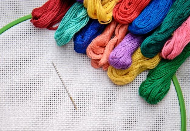 Hilo de bordar multicolor sobre un fondo de bordado con contorno blanco