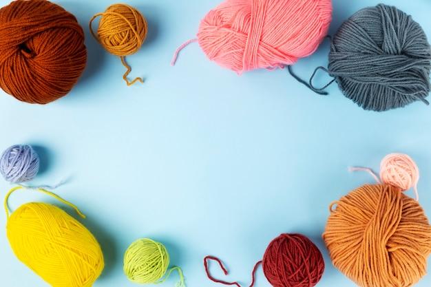 Hilo de color para tejer, agujas de tejer y ganchillo, fondo azul. vista superior. copia espacio