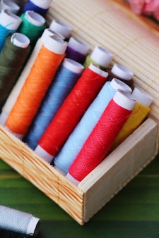 Hilo colorido para coser sobre fondo de madera