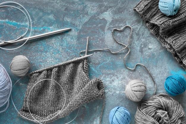 Hilo de lana y agujas de tejer, fondo creativo de tejer en colores azul turquesa