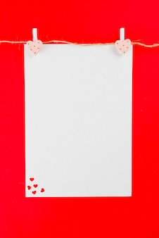 Hilo de lino con hoja de papel en blanco y corazones.