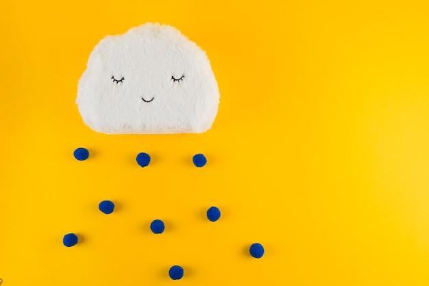 Hilo de nubes blancas con gotas de lluvia azules sobre fondo amarillo