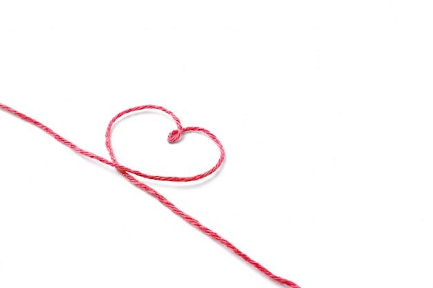 Hilo rojo y corazón aislado en blanco