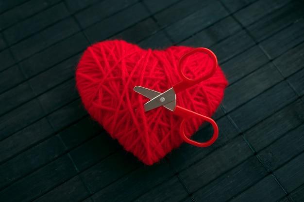 Hilo rojo corazon con tijeras rojas pegadas.