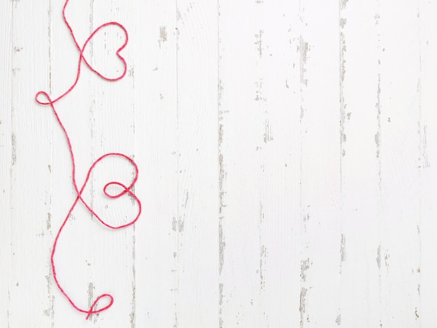 Hilo rojo y dos corazones en madera clara.
