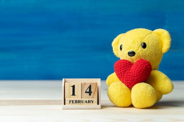 El hilo rojo de la mano hace que el corazón se ponga en un oso de peluche amarillo al lado del calendario de bloques de madera fijado en la fecha de san valentín 14 de febrero