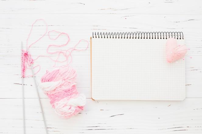 Hilo rosa con ganchillo al lado de la libreta y corazón sobre fondo de madera