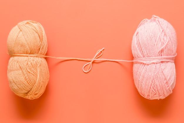 Hilo para tejer atado en lazo sobre fondo naranja.