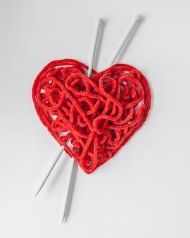 Hilo de tejer rojo con agujas, en forma de corazón.