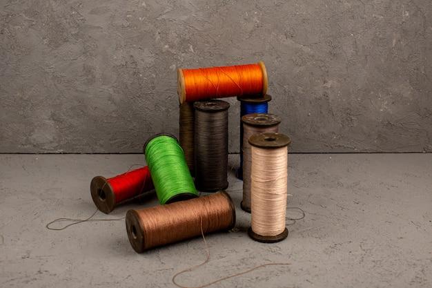 Hilos de colores para coser sobre un fondo gris