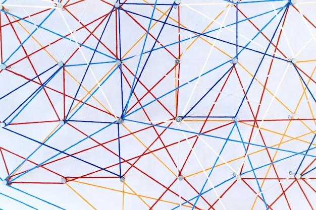 Hilos de colores se estiran en alfileres sobre fondo blanco