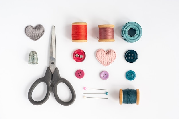 Hilos de coser, agujas, tela, botones y cinta de coser aislado sobre fondo blanco.