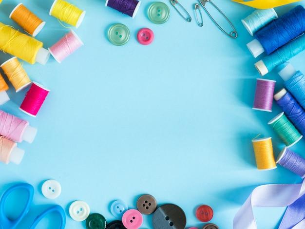 Hilos de coser y botones multicolores en fondo azul con endecha plana del espacio de la copia.