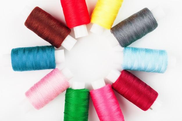 Hilos de coser de diferentes colores en carretes en pentecostés