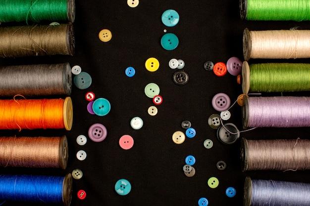 Hilos forrados de colores junto con botones de plástico multicolores sobre un piso marrón