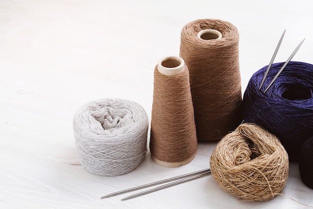 Hilos multicolores, madejas y ovillos de lana italiana, agujas de tejer. el concepto de punto, costura, hecho a mano.
