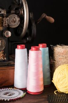 Hilos y agujas cerca de la máquina de coser
