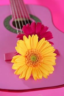 Hippie flor amarillo rosa gerbera en guitarra
