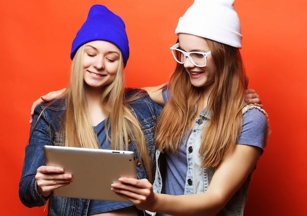 Hipster amigas tomando selfie con tableta digital, estudio