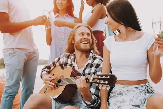 Hipster amigos tocando guitarra y cantando.