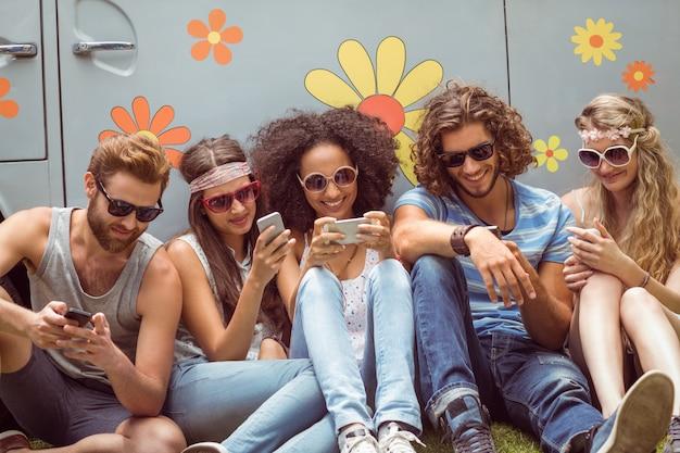 Hipster amigos usando sus teléfonos