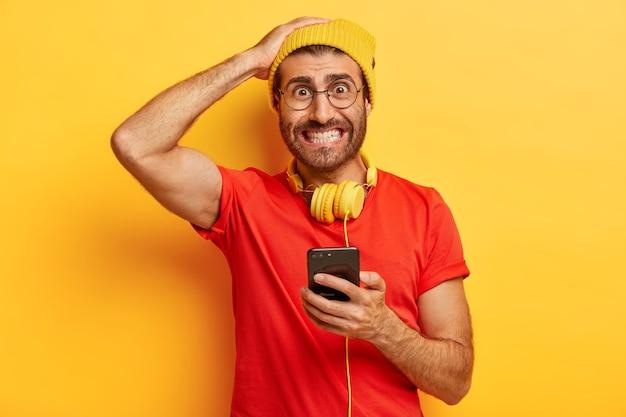 Hipster avergonzado aprieta los dientes, mira nerviosamente, no puede descargar la aplicación necesaria en un teléfono inteligente, tiene auriculares alrededor del cuello, se viste de manera informal