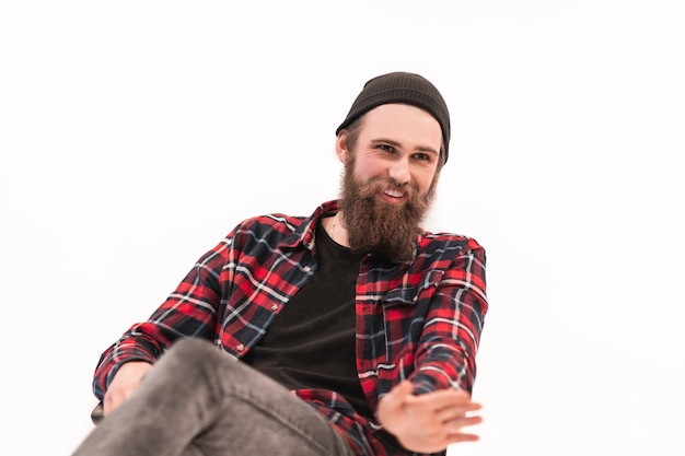 Hipster barbudo con camisa a cuadros explicando algo a su interlocutor.